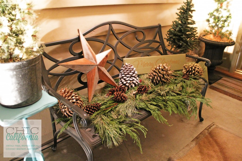 decorating with greenery and pinecones, pinecones, rustic star, merry christmas sign, front porch decorations