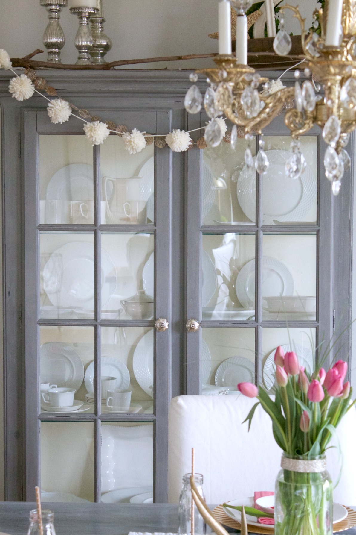 Gray painted china cabinet with white pom pom garland