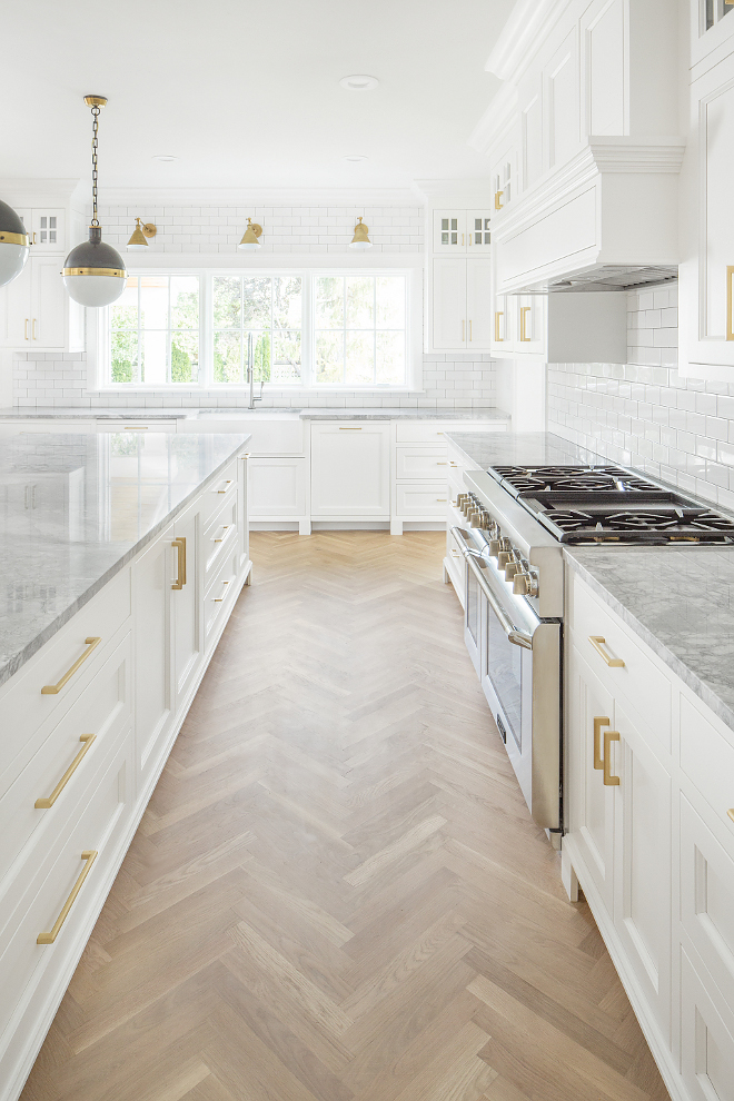 White Kitchen with herringbone wood floors, marble countertops and brass hardware