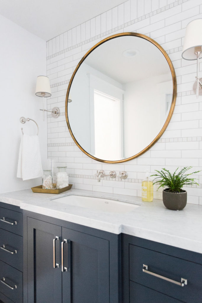bathroom with round brass mirror and shaded sconces, navy cabinets and white countertops