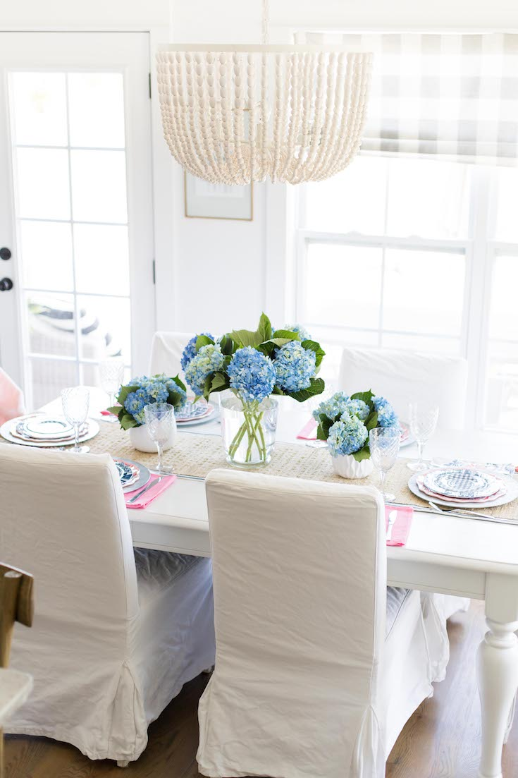 White table with pink and blue dishes, woven table runner and blue hydrangea centerpiece